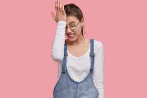 Photo of dissatisfied young woman regrets wrong doing, keeps hand on forehead, clenches teeth, dressed in fashionable outfit, isolated over pink studio wall. Lady forgets something important