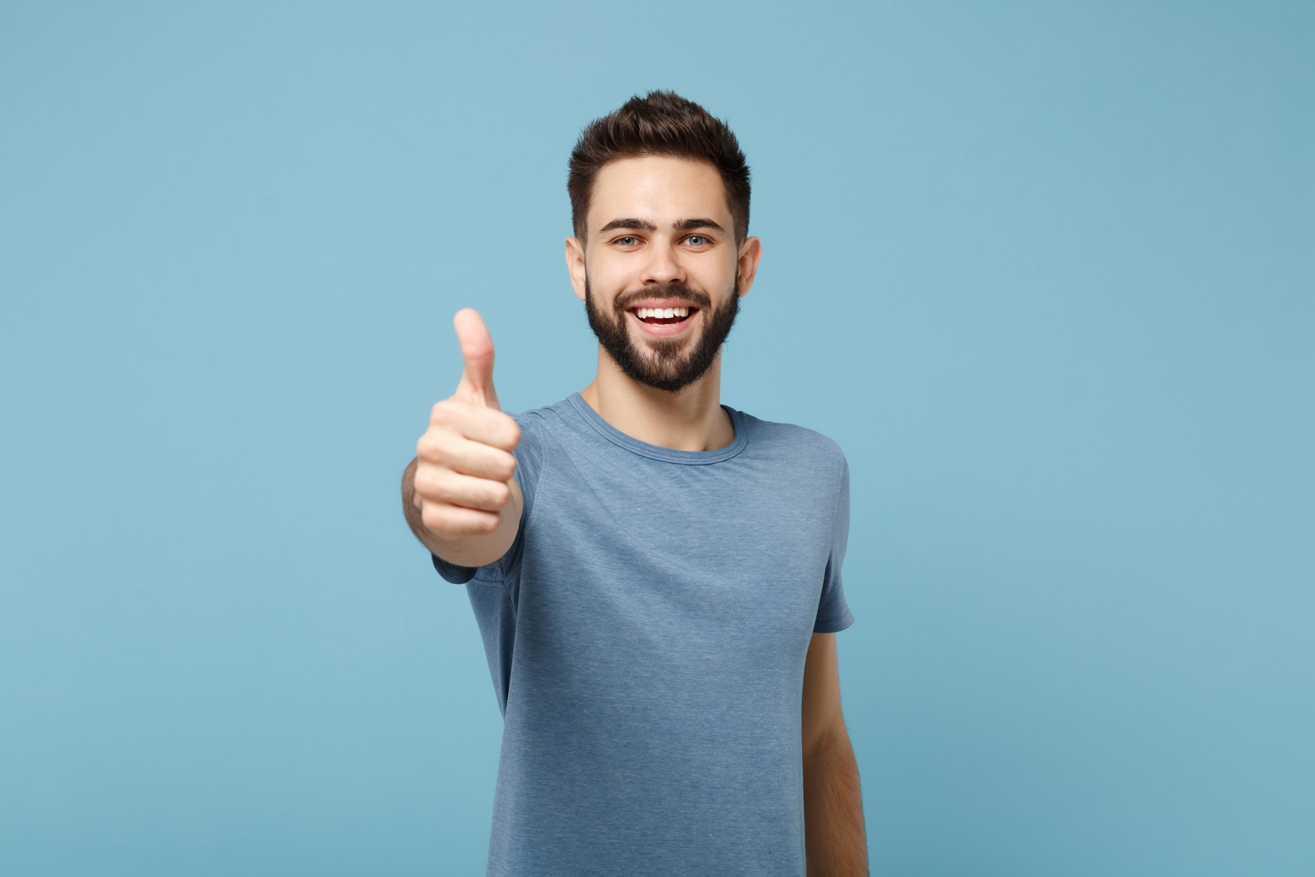 Young smiling cheerful handsome man in casual clothes posing isolated on blue wall background, studio portrait. People sincere emotions lifestyle concept. Mock up copy space. Showing thumb up