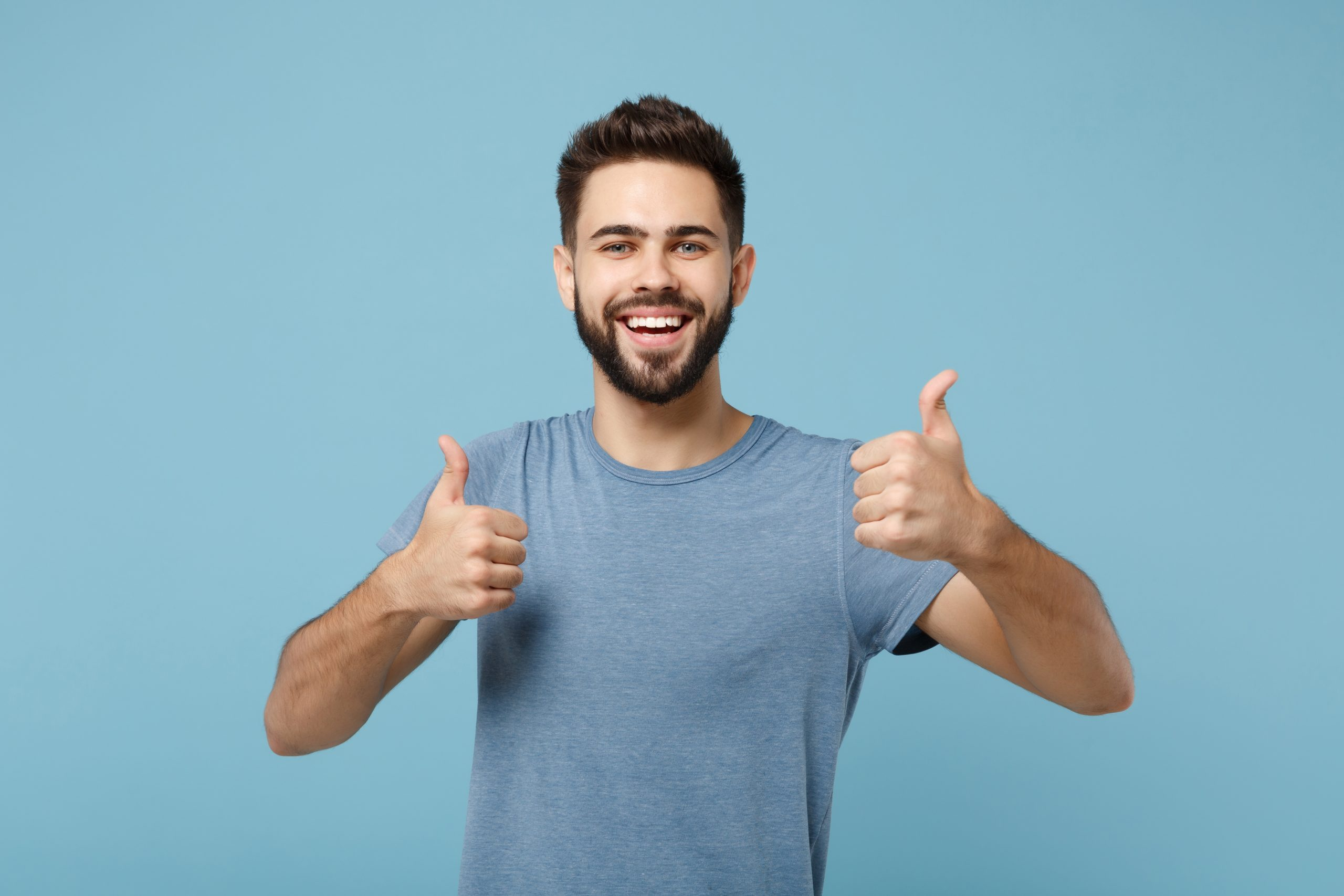 Young joyful funny smiling handsome man in casual clothes posing isolated on blue wall background, studio portrait. People sincere emotions lifestyle concept. Mock up copy space. Showing thumbs up