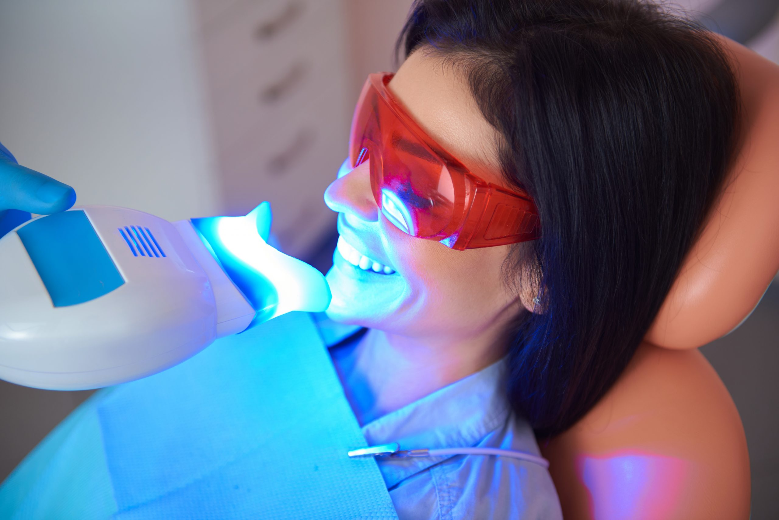Pretty smiling lady in dental room doing teeth whitening
