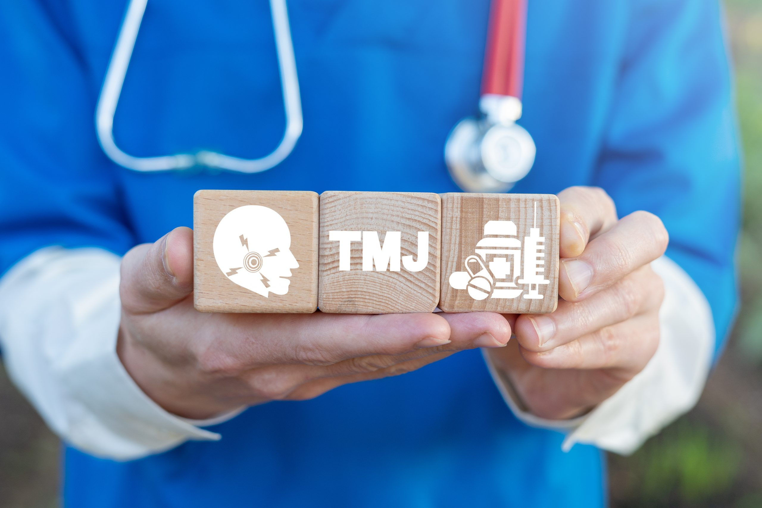 TMJ TMD health care concept on wooden blocks in doctor hands. Temporomandibular Joint and Muscle Disorder Medicine.